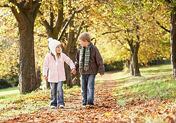 Young boy and young girl outdoors holding hands in a park